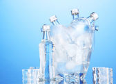 Minibar bottles in bucket with ice cubes, on blue background — Stock Photo