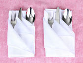 Folded napkin with fork, spoon and knife on color background — Stock Photo