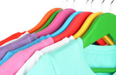 Different shirts on colorful hangers on white background — Stock Photo