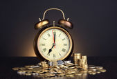 Reloj antiguo y las monedas en la mesa de madera sobre fondo negro — Foto de Stock