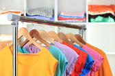 Variety of casual t-shirts on wooden hangers on shelves background — Stockfoto