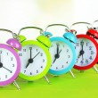 Colorful alarm clocks on table on light background — Stock Photo #29577723