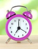 Alarm clock on table on light background — Foto de Stock