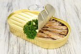 Open tin can with sardines, on wooden background — Stock Photo
