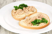 Tasty sandwiches with tuna and cod liver sardines, on white plate. on wooden background — Stock Photo