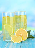 Delicious lemonade on table on blue background — Stock Photo