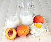 Fresh dairy products with peaches on wooden table close-up — Stockfoto