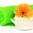 Stock Photo: Rolled green towel, soap bar and beautiful flower isolated on white