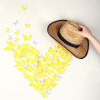 Stock Photo: Paper yellow butterfly in form of heart fly out hat
