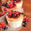 Tasty muffins with berries on wooden table — Stock Photo #29621017