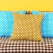 Colorful pillows on couch on yellow background — Stock Photo #29626385