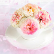 Roses in cup on light pink background — Stock Photo