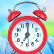 Alarm clock on table on blue background — Stock Photo