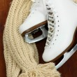 Figure skates with scarf on table close-up — Stock Photo