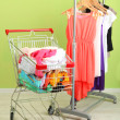 Shopping cart with clothing, on color wall background — Stock Photo #29627653