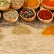 Assortment of spices in wooden spoons on wooden background — Stock Photo #29627679