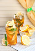 Iced tea with lemon and mint on wooden table — Stok fotoğraf