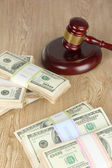 Stacks of money and judges gavel on wooden table — Stock Photo
