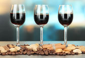 Glasses of liquors with almonds and coffee grains, on bright background — Stock Photo
