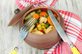 запеченный смешанных овощной с куриной грудкой в котелке, на фоне деревянных — Стоковое фото