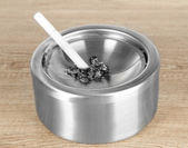 Metal ashtray and cigarette on wooden table — Stock Photo