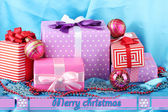 Colorful gifts with pink Christmas balls, snowflakes and beads on blue background — ストック写真