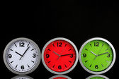 Round office clocks on black background — Stock Photo
