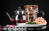 Kettle glass cup of ice tea from tea rose on metallic tray on napkin on black background — Stock Photo