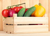 Fresh vegetables in box on wooden background — Stock Photo