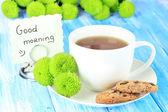 Vackra gröna krysantemum med kopp te på bordet närbild — Stockfoto