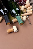 Bottles of wine, grapes and corks on brown background — Stock Photo