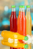 Bottles with tasty drinks with ice cubes, on bright background — Stock Photo