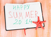 Notepad with sign 'Happy summer' Concept of vacation planning. On color wooden background — Stock Photo