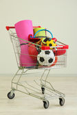 Shopping cart with sport equipment, on gray background — Stock Photo
