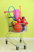 Shopping cart with sport equipment, on green wall background — Stock Photo