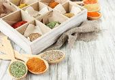 Variedade de especiarias na caixa, no fundo de madeira e colheres de pau — Foto Stock