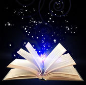 Open book with blue magic light and falling stars on dark background — Stock Photo