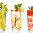 Stock Photo: Glasses of fruit drinks with ice cubes isolated on white