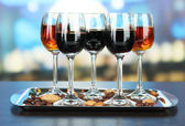 Glasses of liquors with almonds and coffee grains, on tray, on bright background — Stock Photo