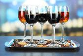 Copas de licores con almendras y granos de café, en la bandeja, sobre fondo brillante — Foto de Stock