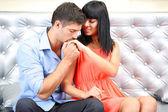 Beautiful young romantic couple sitting on sofa — Stock Photo