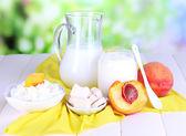 Productos lácteos frescos con duraznos en mesa de madera sobre fondo natural — Foto de Stock