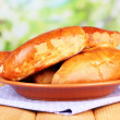 Fresh baked pasties, on wooden table, on bright background — Stock Photo