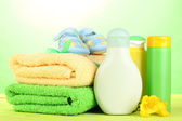 Baby cosmetics, towels and boots on wooden table, on green background — Stock Photo
