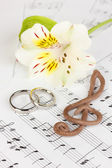 Treble clef, flower and wedding rings on musical background — Stock Photo