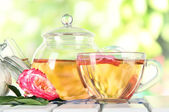 Kettle and cup of tea from tea rose on napkin on wooden table on nature background — Stock Photo