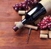 Bottle of wine, grapes and corks on wooden background — Stock Photo