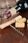 Corkscrew with wine corks and bottle of wine on wooden table close-up — Stock Photo