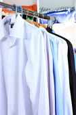 Variety of casual shirts on wooden hangers on shelves background — Stock Photo