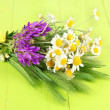 Wild flowers and green spikelets, on wooden background — Stock Photo
